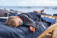kid sleeping on deckchairs at the beach
