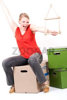 junge Frau mit Haussymbol sitzt auf Umzugskartons