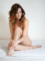 naked woman covering body while sitting on bed