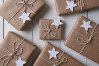 Top view of a group of plain paper wrapped Christmas presents with blank wood star gift tags.