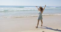 Female walking along the shore of beach