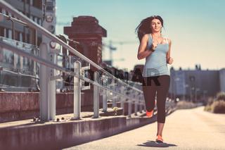 City workout. Beautiful young woman running in an urban setting