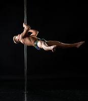 Male pole dance. Strong guy dancing in studio