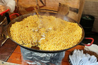 Street fast food - boiled yellow peas with bacon, garlic and fat  in a big iron frying pan.