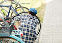 man fastening bicycle lock on street parking