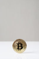 bitcoin cryptocurrency physical coin standing upright on desk