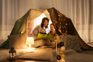 happy family reading book in kids tent at home