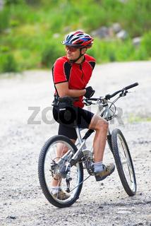 Mountain biker waits on rural road