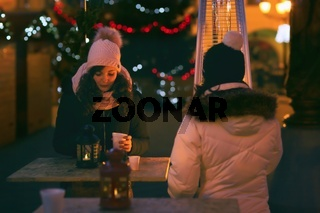 People outdoors sipping christmas punch on Christmas Eve.