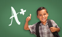 Hispanic Boy with Thumbs Up in Front of A+ Written on Chalk Board