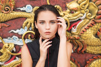 Fashion closeup of young brunette woman over golden dragon on the wall