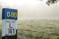 Marker sign on a highway in the fog