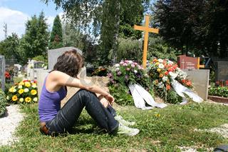 Junge Frau trauert bei einem frischen Grab