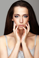 Beauty portrait of young woman touching face with fingers. Brunette girl with long hair and day female makeup on gray background