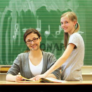 Junge freundliche Lehrerin und Schülerin im Klassenzimmer - quadratisch -
