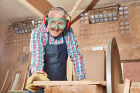 Senior schleift Holz an Schleifmaschine