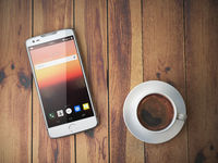 Mobile phone and coffee cup on wooden background.