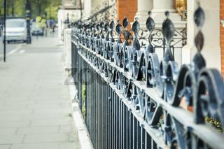 Ein Schmiedeeiserner Zaun entlang eines Bürgersteiges in London, England, GRoßbritannien.