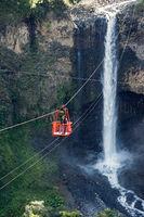 Tourists gliding on the zip line trip against Bridal veil (Manto de la novia), waterfall in Cascades route, Banos de Agua Santa