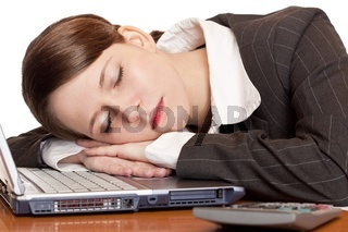 Müde überlastete Frau schläft im Büro auf Laptop
