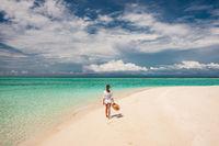 Woman with sun hat on tropical beach