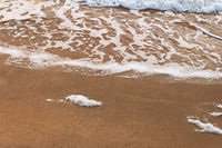 Sea wave over sand with foam on its top