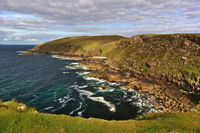 Rocky coast with steep cliffs, waves, sky, clouds