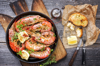 Traditional fried black tiger prawn with garlic bread as top view in a black frying pan