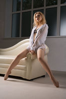 Pretty blonde in white shirt posing on a sofa