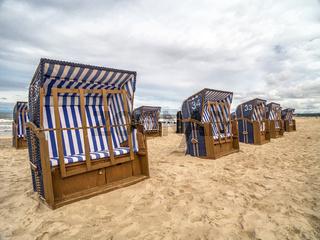 Empty roofed wicker beach chairs on sandy beach in Ustka resort