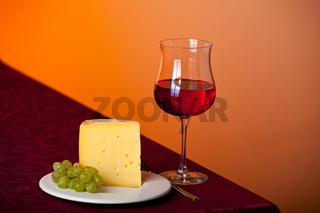 Stück Käse, eine Traube und Rotwein