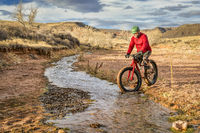 riding a fat bike across a stream