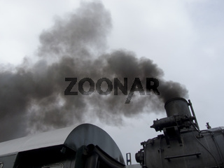 Schwarzer Rauch aus einem Schornstein einer alten Dampflok