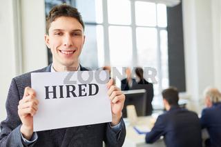 Junger Mann freut sich über einen neuen Job