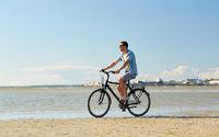 happy man riding bicycle along summer beach