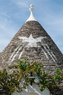 Symbol in the Trullo conical rooftop in Alberobello, Puglia, Italy