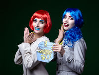 Portrait of young women in comic pop art make-up style on dark background. Female detectives investigate a crime with casket of jewelry in hands
