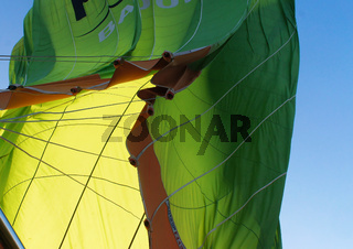 View from below onto the collapsing envelope of a green hot-air balloon, Cappadocia, Anatolia