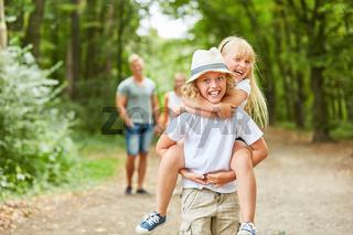 Junge trägt lachende Schwester huckepack