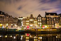 Beautiful night in Amsterdam. Night illumination of buildings and boats.