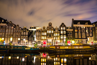 Beautiful night in Amsterdam. Night illumination of buildings and boats.