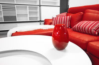 Red vase on a table in a stylish living room