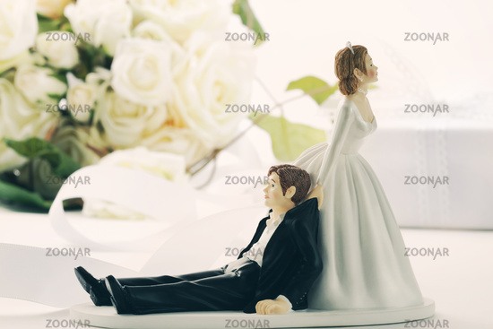 Closeup of whimsical wedding cake figurines on whi