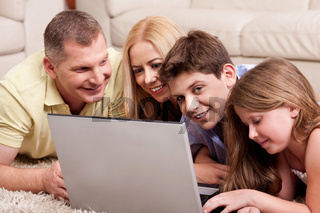 Happy family of four browsing on laptop as they relax on carpet in living room