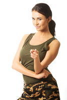 Woman in military clothes pointing on you