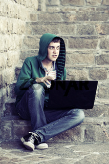 Young man with laptop sitting on the steps