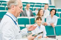 Älterer Dozent mit Tablet unterrichtet Studenten