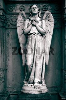 Betender Engel aus Stein auf einem Friedhof