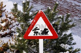 Schild mit Weihnachtsmann auf Schlitten und Rentier im Winter - Road sign with Santa Claus on sledges and reindeer in winter