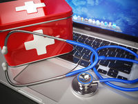 First medical aid or technical support concept. Laptop with first aid kit and stethoscope